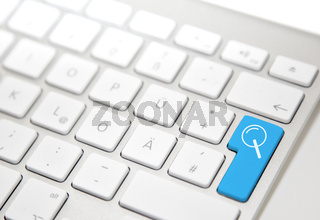White computer keyboard with blue 'search' button