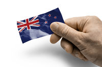 Hand holding a card with a national flag the New Zealand