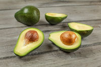 Avocados cut in half seed visible, one whole green pear in background, on gray wood desk