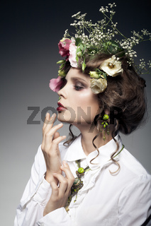 portrait of beautiful young woman with flowers in hair isolated on dark background