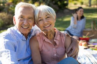 Portrait of happy senior couple sitting in the park