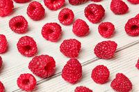Raspberries spilled on white boards desk.