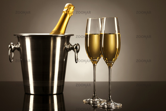 two glasses of champagne with a champagne bucket