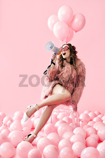 Trendy young woman shouting in megaphone on pink balloons background