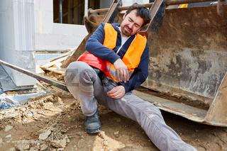 Arbeiter auf der Baustelle schläft auf Baggerschaufel