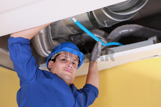 Plumber holding a blue pipe above a ceiling