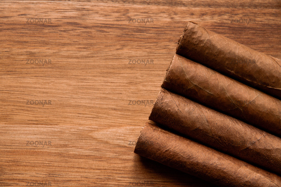 Group of brown cuban cigars on wooden background