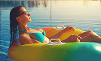 Woman sit in rubber donut in swimming pool