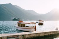 A white sailboat with a sun canopy is moored to the pier in Perast, Montenegro, against the backdrop of the island of Gospa od Skrpella.