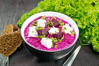 Soup puree of beetroot with salted cheese in bowl on dark board