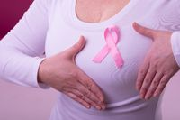 Midsection of caucasian woman in white tshirt with pink ribbon gesturing