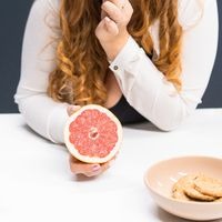 Fat young woman holding a fresh grapefruit in hand standing leaned on a kitchen table at home with long curly blond hair. Dieting and nutrition concept. Square cropped