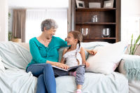 Senior Caucasian woman watching a family album at home with her granddaughter