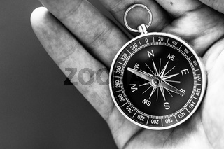 Innovation concept: Man is holding a compass in his hand, closeup cutout