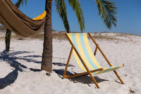 Magnificent view of a beach with a deck chair and a palm tree