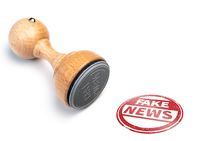 round FAKE NEWS rubber stamp and red imprint