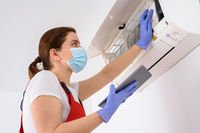 Female technician using digital tablet and repairing air conditioner