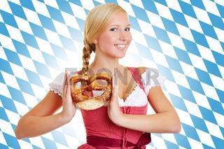 Frau im Dirndl mit Brezel vor bayrischer Flagge