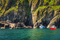 Boats docking to per on Skellig Michael island, tourists on and of boarding