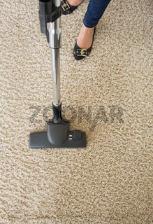 Carpet being hoovered by woman