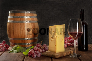 A glass of red wine with a bottle, a wine barrel, a large piece of cheesse, grapes, and vine leaves