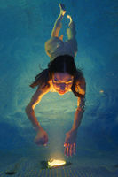 Female swims in geothermal pool, reaches out hands to illuminated lights from pool lamp at night