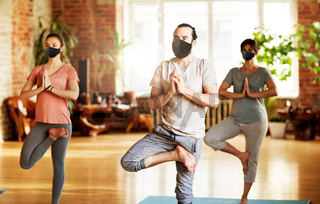 group of people in masks doing yoga at studio