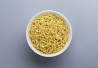 Instant noodles in white plate, top view