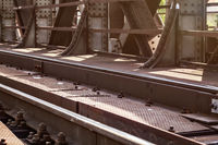 Rail bridge, detail on tracks, steel plates, large nuts and bolts lit by sun.