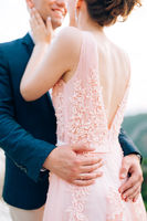 the groom and the bride embrace tenderly, the bride has a beautiful dress with an open back