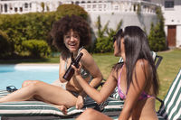 Two diverse female friends sunbathing by pool and drinking beer