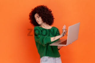 Portrait of emotional young curly woman on orange background.