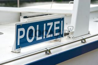 Schild mit der Aufschrift Polizei auf einem Polizeiboot