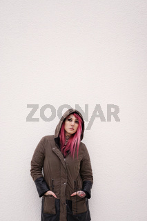 young woman with pink hair piercings and tattoos against wall with copy space