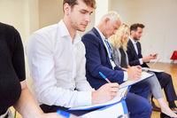 Seminar Teilnehmer mit Klemmbrett machen sich Notizen