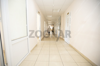 Long hospital corridor with a silhouette of a doctor in a protective suit.