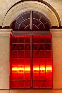 Rot beleuchtetes Fenster an historischer Hausfassade