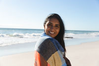 Portrait of smiling mixed race woman on beach holiday looking to camera