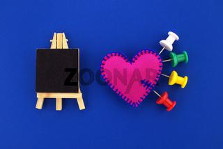 Medical concept with thumb tacks stuck into a felt heart