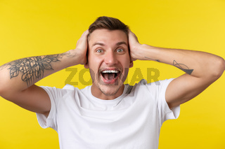 Lifestyle, summer and people emotions concept. Close-up portrait of extremely happy rejoicing young man looking surprised, cant believe he won prize, hold hands on head in denial, yellow background