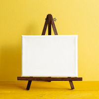 Easel with blank canvas on wooden table. yellow wall background