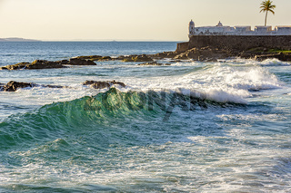 Salvador sea waves with old colonial fortress in the background