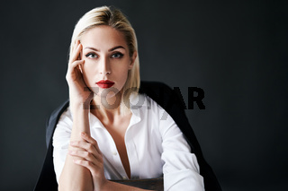 Close up portrait of beautiful blonde woman with red lips in elegant white shirt and black jacket posing isolated on black studio background