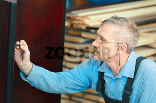 Portrait of an elderly carpenter at work in a carpentry shop.