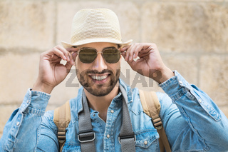 Stylish traveler bearded man in hat posing looking at camera, travel and wanderlust concept.