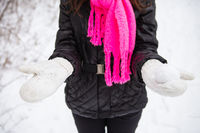 Young woman holding natural soft white snow in her hands to make a snowball, smiling on a cold winter day in the forest, outdoors.