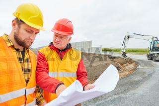 Architekt und Bauleiter mit Bauzeichnung auf Baustelle