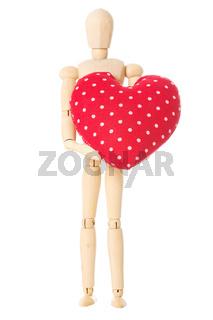 Eine Modellpuppe aus Holz die ein rotes Herz aus Stoff hält vor einem weißen Hintergrund