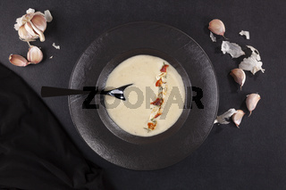 Garlic cream soup in black plate over dark background from above.