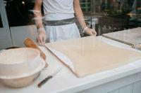 A man prepares an apple strudel for sale. Prepares the dough